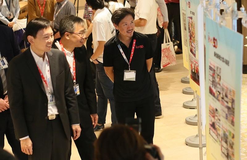 本报总编辑朱志伟(中)陪同通讯及新闻部政务部长徐芳达(左)及新加坡报业控股副执行长陈康威一同欣赏本报图片展作品。(陈佩敏 摄影)