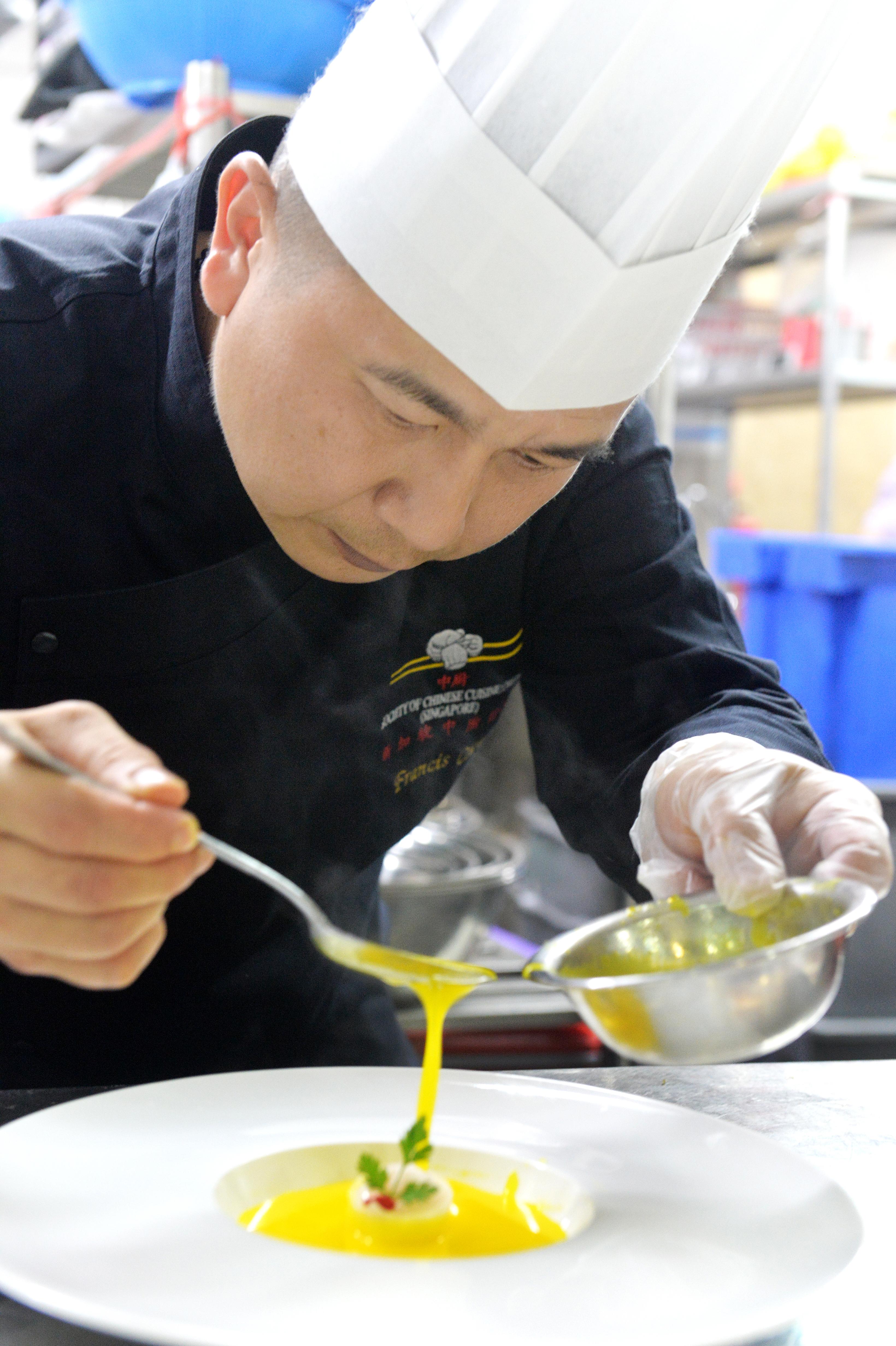 """中厨协会会长张伟忠聚精会神为汤品""""极品龙皇白玉球""""摆盘。"""