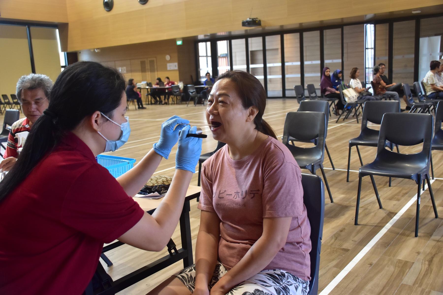 丽珍让护理人员检查牙齿和口腔,她也学到如何保护敏感牙齿。(图/卫生部提供)